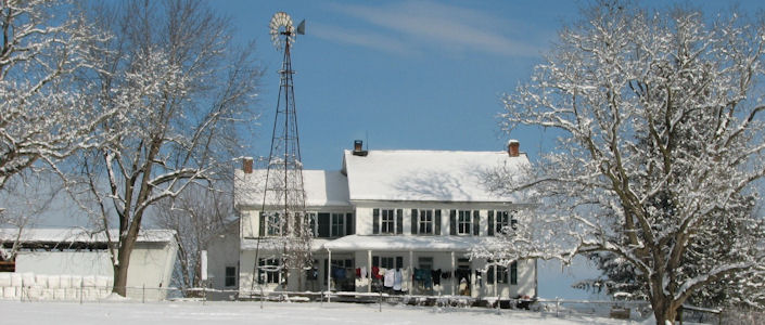 Amish house in snow with clothes hanging on the porch